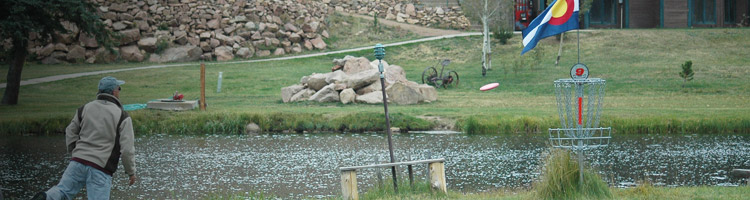 image of a disc golfer putting at a basket on the Beaver Meadows course in Red Feather Lakes, Colorado